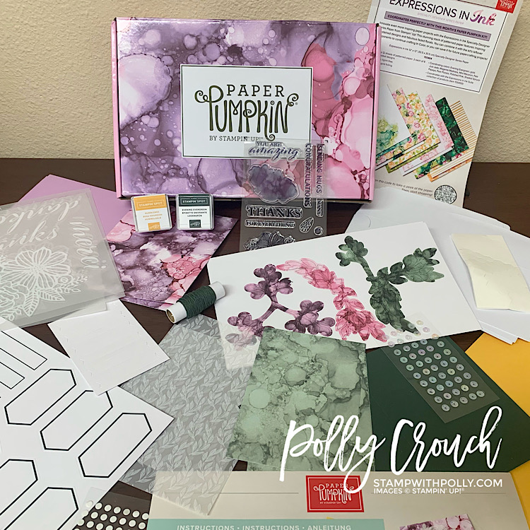 This is a picture of the June Paper Pumpkin kit called Expression In Color.  The picture includes the card bases, vellum cutouts, embellishments including ribbon and sequins and a stamp set and two ink spots.