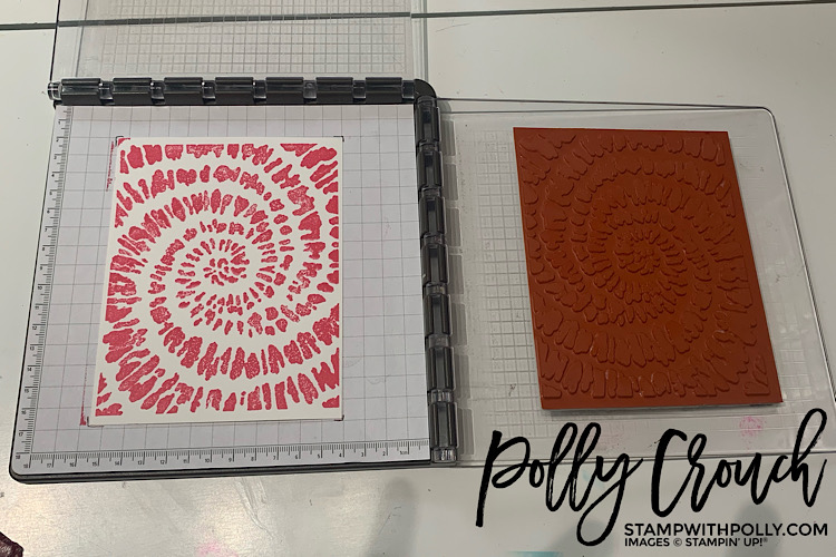 This is an image of white cardstock laying in the center of the Stampartus stamped with the Spiral Dye stamp in Polished Pink ink.