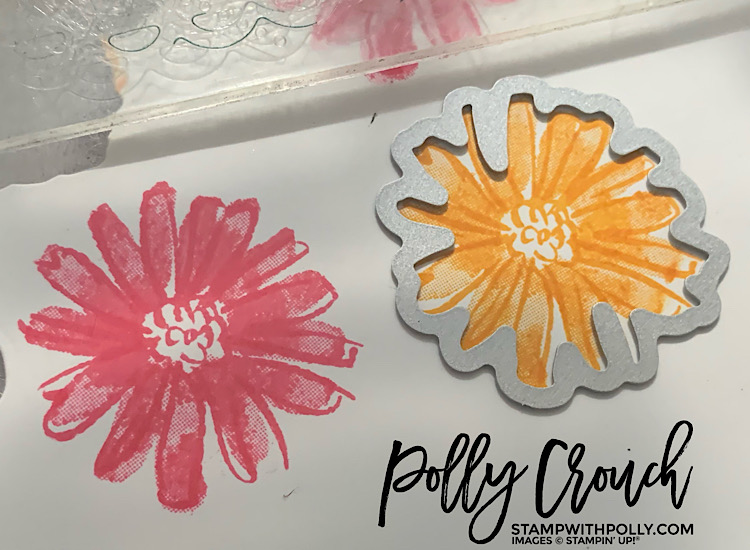 This is an image of stamped daisies in Mango Melody and Polished Pink with a die laying on one of the daisies getting ready to be cut.